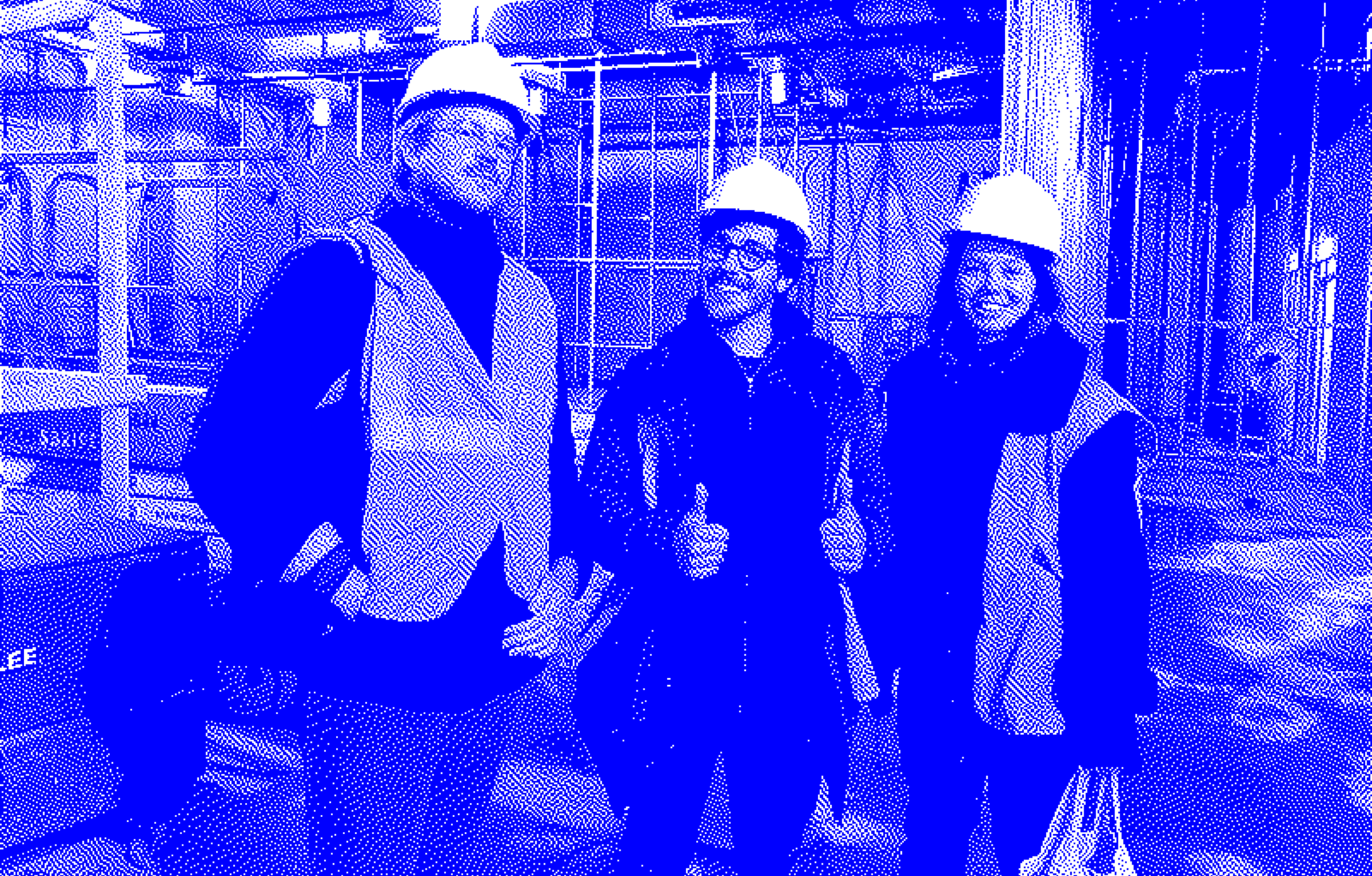 Hugh Francis, Sebastian Odell, and Isabel Münter of Sanctuary Computer wearing hardhats at an indoor construction site