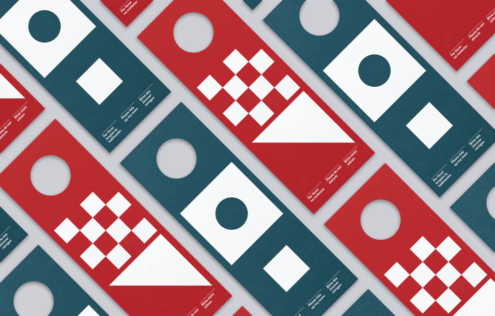 Door tags for the Eolo Hotel. Design by Atlas. The tags, which are blue and red, feature text and geometric patterns in white.