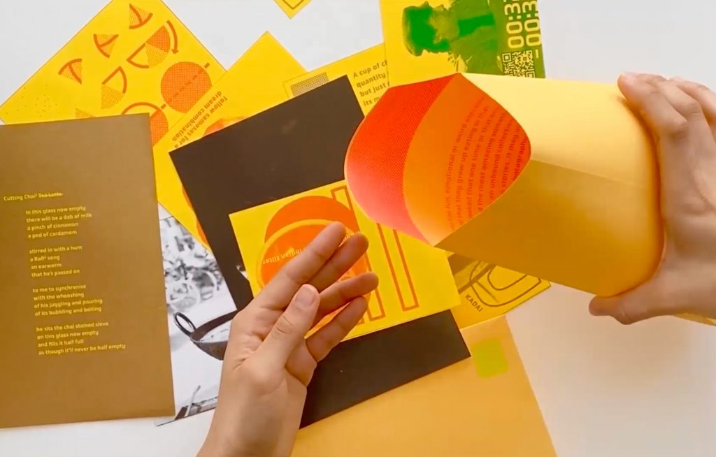 Photograph depicting hands holding a manila envelope; spread on a surface beneath them are colorful printed texts