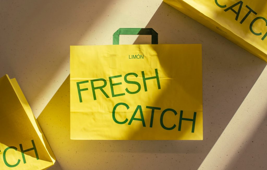 Bright yellow paper bags with green handles and the words LIMÓN and FRESH CATCH in green type.