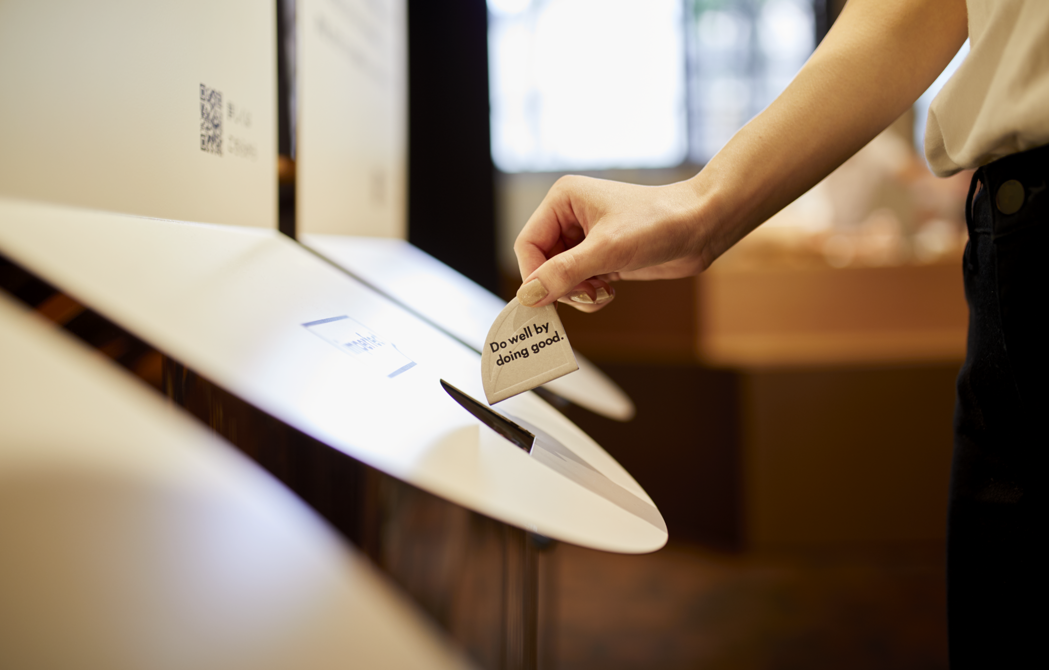"View of a woman inserting a token into a collection bin at Imperfect, a socially conscious café in Tokyo. The token reads, ""Do well by doing good."""