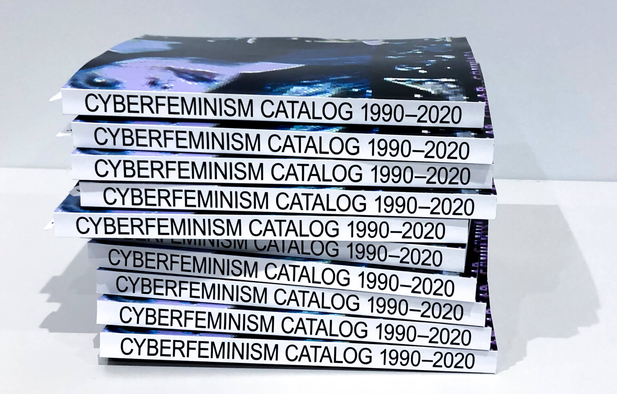 Stacked copies of Mindy Seu's Cyberfeminism Catalog, 1990–2020