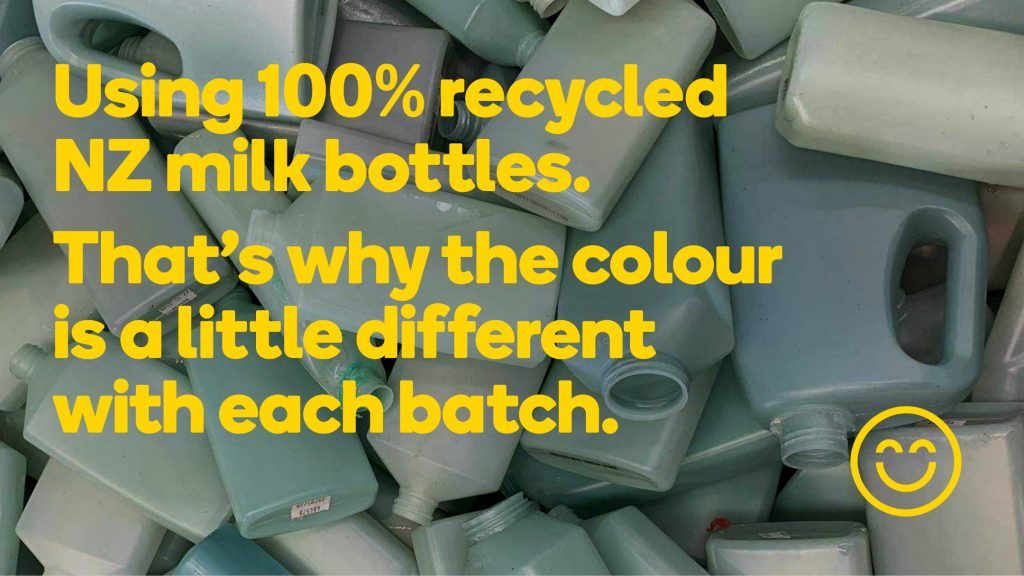 """Over a picture featuring a pile of multicolor plastic bottles is the phrase """"Using 100% recycled NZ milk bottles. That's why the colour is a little different with each batch"""" in yellow type."""